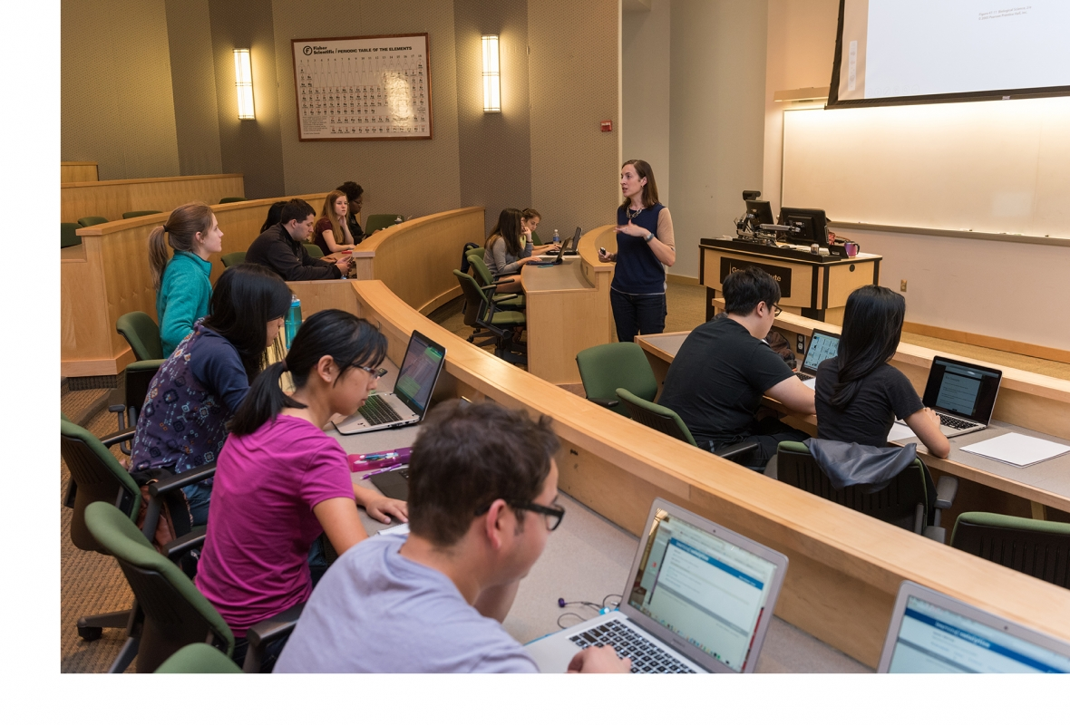 Students on Laptops listening to a lecturer in an auditorium classroom